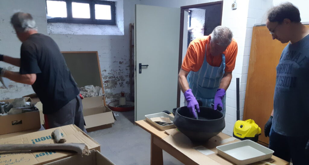 Während der Arbeit im Kellerraum: Friedhelm Raute, Bernd Wingender und Willi Köster (v.l.n.r.) befreien die Funde vom Staub mittels Absaugung.